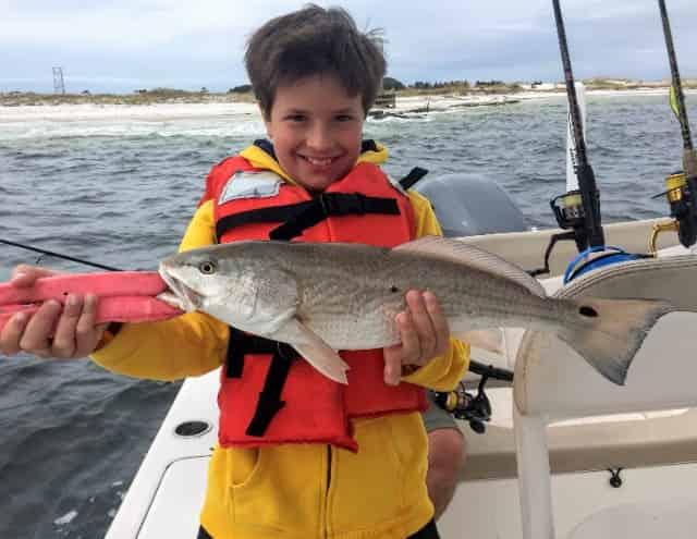 destin coastal life adventures and charters kid holding redfish