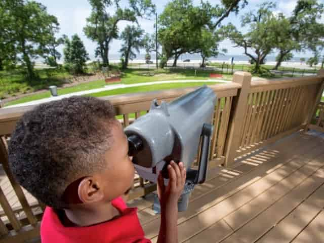 child with a telescope at lynn meadows discovery center